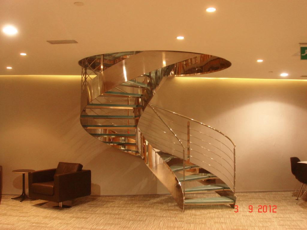 Escalera helicoidal de acero inoxidable brillo espejo y peldaños de cristal